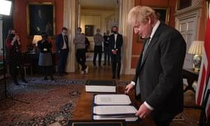No 10 staff watching as Boris Johnson signs the bill.