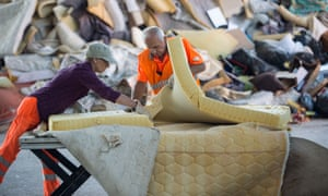 Workers dismantle a mattress in a recycling plant in Darmstadt, Germany