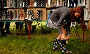A festival-goer tries on wellington boots at the Glastonbury Festival, UK.