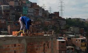 Valdinei lays bricks on a three-storey home in Santo André favela, São Paulo, Brazil, August 2016.