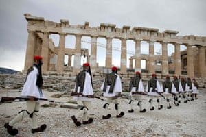 Members of the Presidential Guard walk in front of the Parthenon temple in Athens, Greece