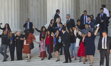 Supporters of immigration reform hold hands as they leave together after hearing arguments at the supreme court.