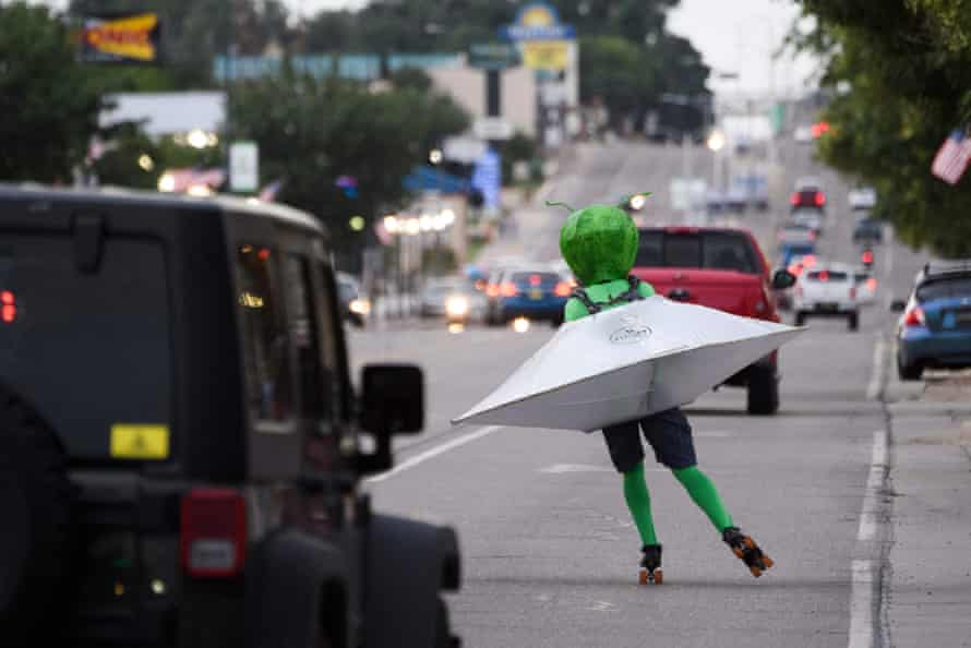 A person wearing an alien costume in a flying saucer roller skates through traffic down Main Street during the UFO Festival in Roswell, New Mexico