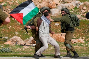 A Palestinian protester is detained by Israeli soldiers near the West Bank village of Tubas during a demonstration against Donald Trump's peace proposals.