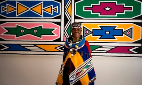 Esther Mahlangu poses in front of one of her artworks at the Melrose Gallery in Johannesburg