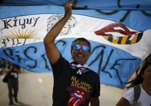 Fans carry an Argentinian flag on their way to the Ciudad Deportiva de la Habana sports complex where the Rolling Stones' free outdoor concert will take place