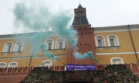 Feminist activists unfurl a banner with a message reading 'Men have been in power for 200 years. Down with it!' and light smoke flares outside the Kremlin on International Women's Day.
