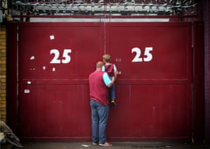 A father lifts his son up to look through a gap in the gates of Upton Park as West Ham United play their last game at the ground