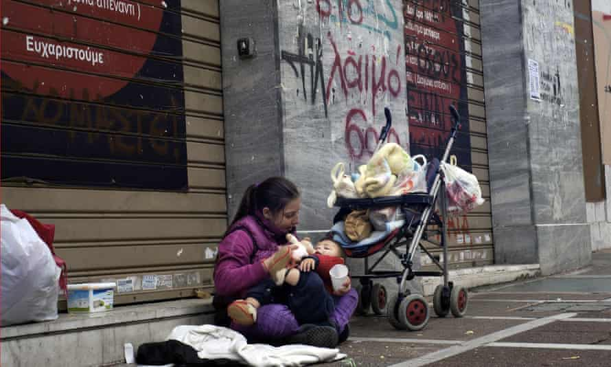 A woman with a child begs on an Athens street.
