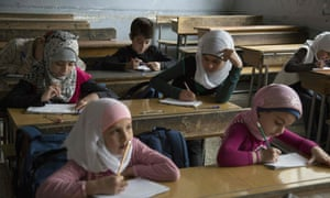 Syrian children attend a class at a primary school in Aleppo's rebel-held eastern district of Shaar on 7 May 2016