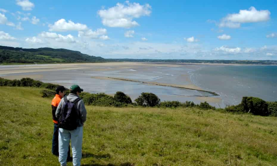 Hikers overlooking Llanddona beach and Red Wharf Bay, Anglesey, with the fish trap exposed at low tide.