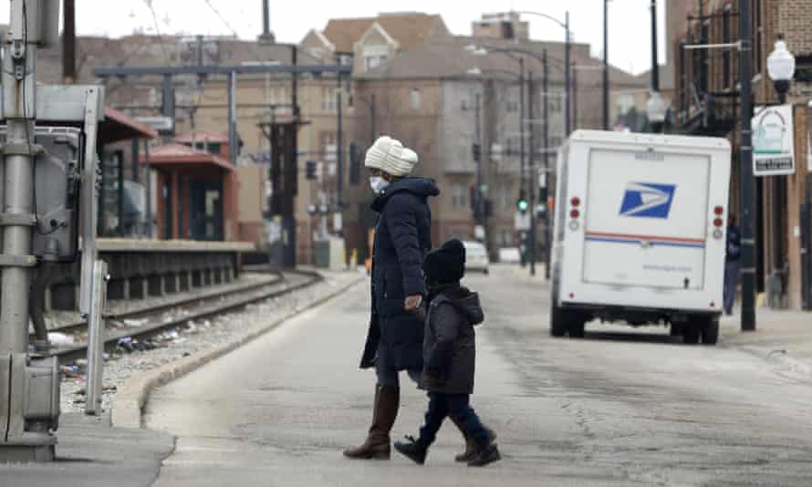 Pedestrians wear mask as they cross the street in Chicago on 22 April.