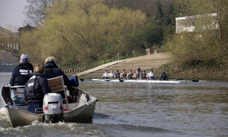 Members of the Thames Rowing Club in Putney follow female crews training for the boat race.