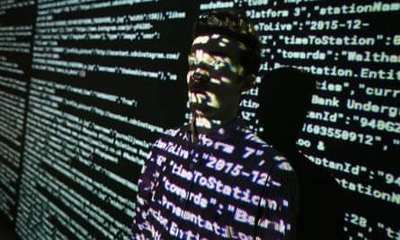A person stands in front of a screen showing computer code.