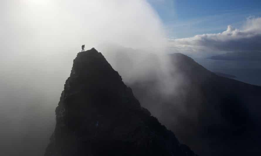A lone climber stands on a mountain summit in the Black Cuillins, with a mist shrouded sun behind him, Isle of Skye, ScotlandBEP7EB A lone climber stands on a mountain summit in the Black Cuillins, with a mist shrouded sun behind him, Isle of Skye, Scotland