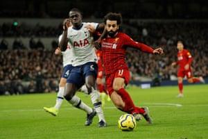 Davinson Sanchez challenges Mohamed Salah.