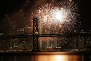 Fireworks light up the sky over the San Francisco-Oakland Bay Bridge and the city skyline