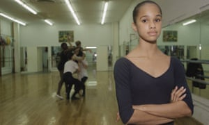 Misty Copeland in 1998, as a child in a dance studio, in a black leotard, her arms folded.
