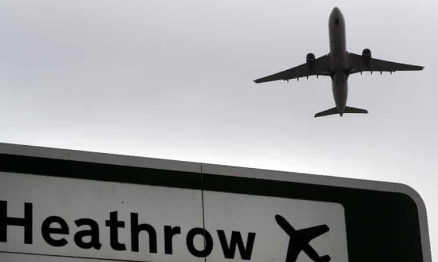 A plane takes off over a road sign for Heathrow airport in London.