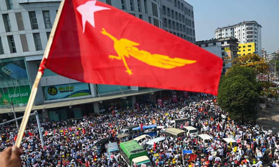 a protester waves the National League for Democracy (NLD) flag while others take part in a demonstration against the military coup in Yangon.