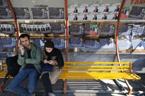 A couple waits for a bus on Vali Asr Avenue in Tehran.
