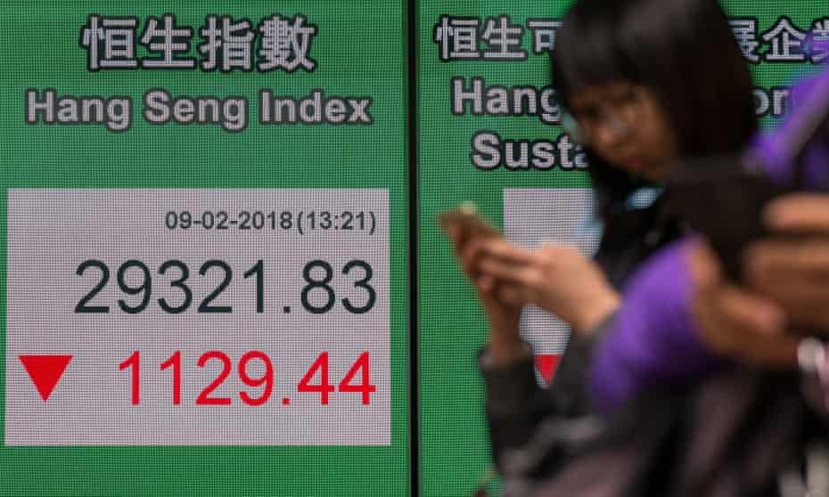 Pedestrians walk past an electronic display showing the Hang Seng Index in Hong Kong, China.