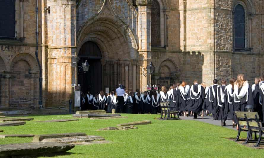 Durham, County Durham, England. University graduands queuing to enter the cathedral prior to their graduation ceremony.