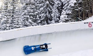 A blue bobsleigh on a run with snowy trees in the background
