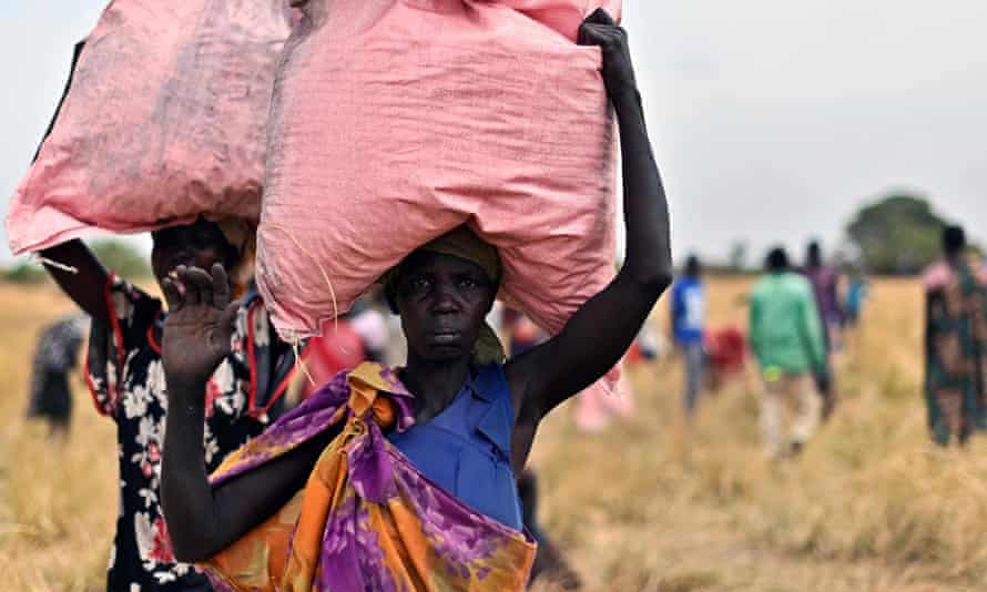 Villagers in South Sudan collect food aid dropped from a plane