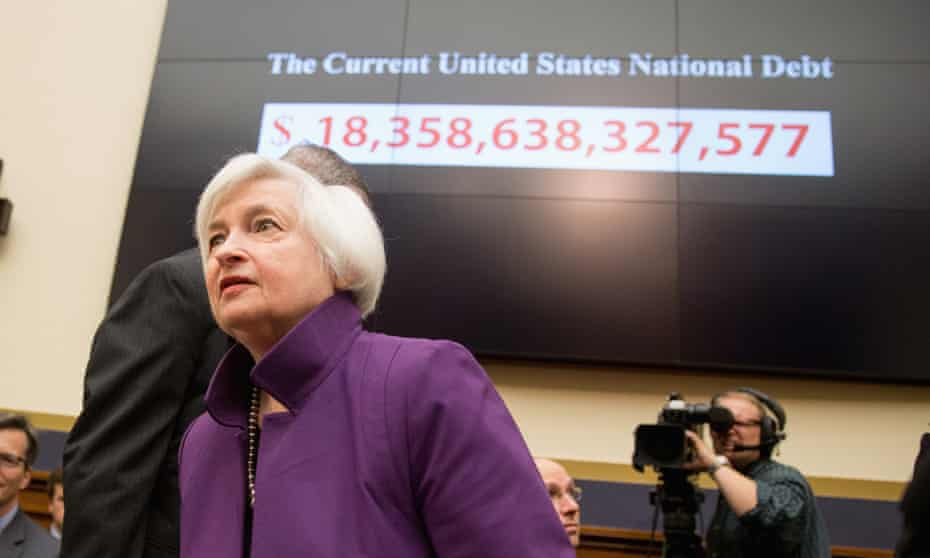 Federal Reserve chair Janet Yellen passes a national debt banner as she arrives on Capitol Hill in Washington on Wednesday.