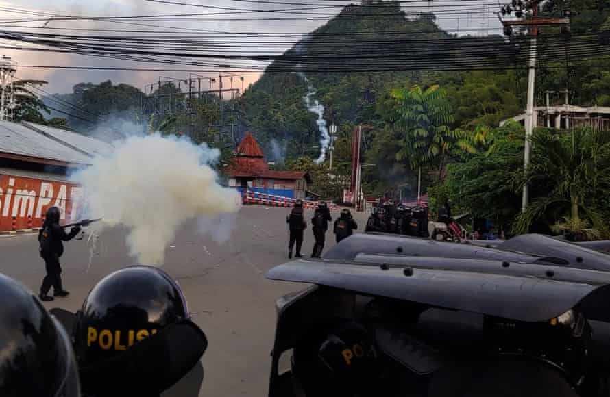 Riot police officers fire tear gas during a protest in Jayapura, Papua.