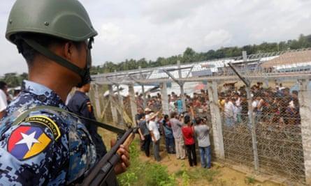 A Myanmar border guard watches Rohingyas refugees on the Bangladesh border.
