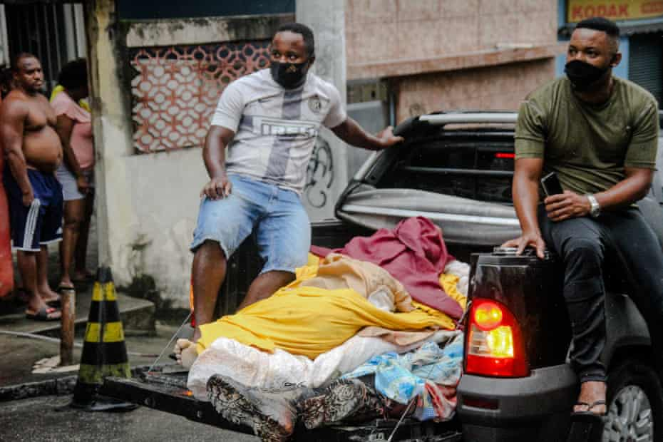 Residents remove bodies from Rio's Complexo do Alemão favela on Friday after the police operation.