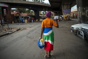 A woman living near the traditional medicine market walks away with food baskets following a distribution by private donors on 13 April.