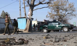 Afghan security officials inspect the scene of a roadside bomb blast last week.