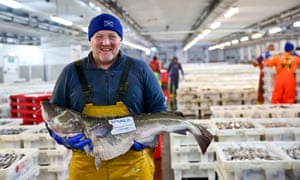 David Milne, skipper of the MSC-certified trawler Adorn, holds a cod in Peterhead fish market.