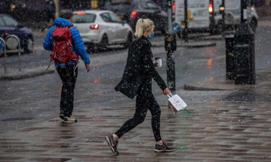 Commuters make their way to work through a spring snow blizzard in Wimbledon, south-west London
