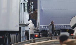 Migrants trying to board UK bound trucks on the main road into Calais ferry port.