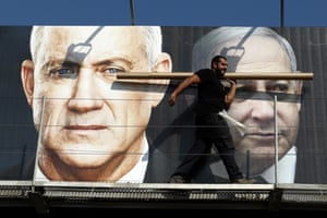 Tel Aviv, Israel: A labourer walks past a banner depicting the prime minister, Benjamin Netanyahu, right, and Benny Gantz, the leader of Blue and White party
