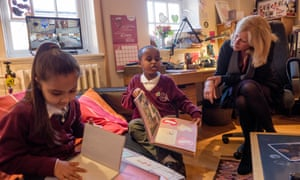 The headteacher of Avondale primary school near Grenfell Tower accompanies pupils as they look at memory books made to help them deal with grief.