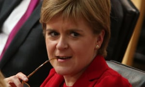 Nicola Sturgeon smiles nervously, spectacles leg between her teeth, after outlining her legislative programme at Holyrood