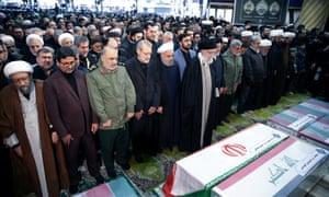 Iran's supreme leader, Ayatollah Ali Khamenei, and President Hassan Rouhani pray near the coffins of Qassem Soleimani