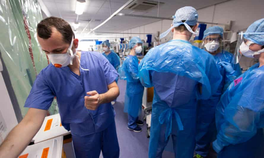 Doctors take off their PPE as they leave a Covid intensive care unit