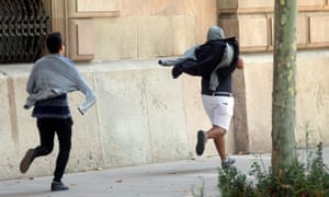 Two of the defendants run away from the court after the opening day of their trial in Barcelona.