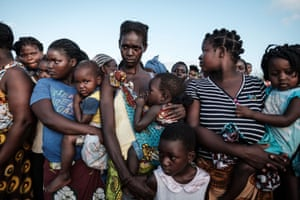 Mothers wait with their children to receive food from a local supermarket in Dondo, about 35km north from Beira