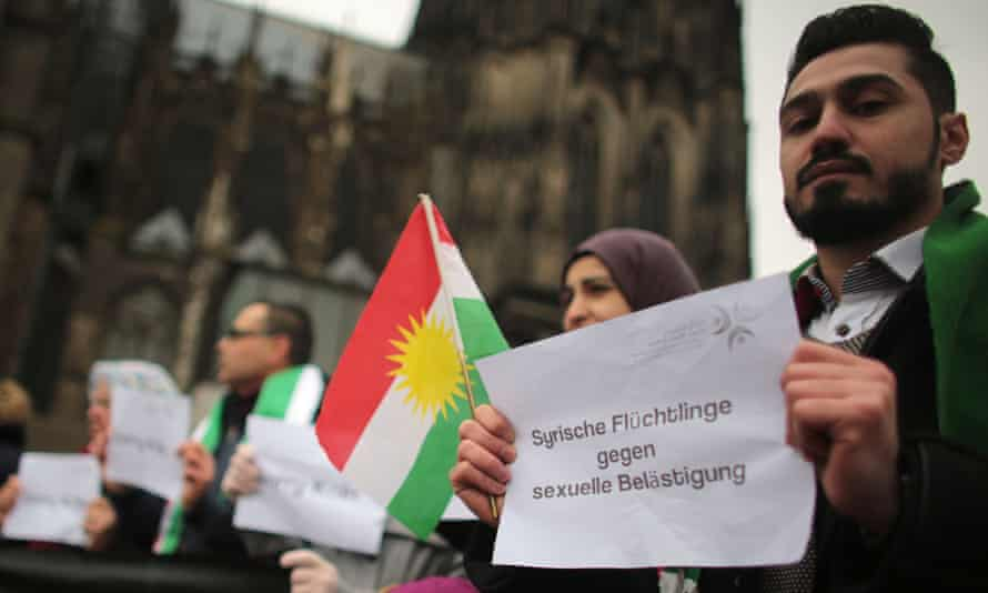 Refugees from Syria carry signs reading 'Syrian refugees against sexual harassment', after a string of attacks in Cologne on New Year's Eve.