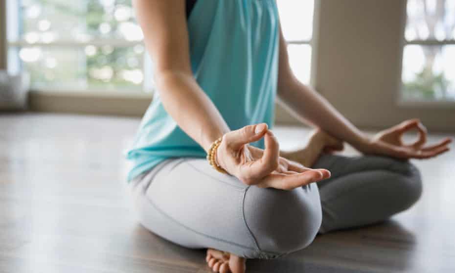 Woman in lotus position practicing mudra meditation
