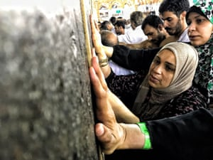 Men and women touch the Ka'bah stone as they walk around Islam's holiest site, located in the centre of the Masjid al-Haram (Grand Mosque) in the holy city of Mecca.