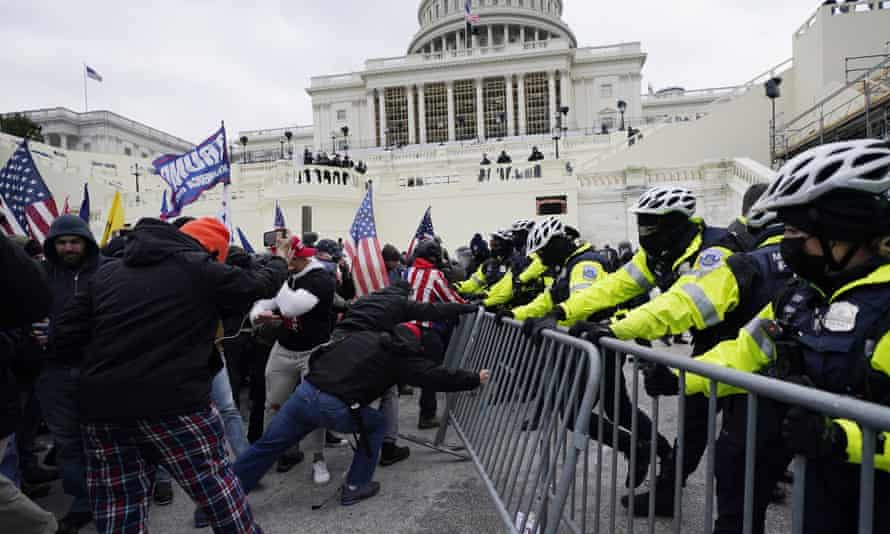 Members of a mob try to break through a police barrier at the US Capitol in Washington DC on 6 January.