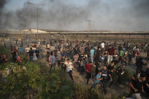 Palestinian protesters run from teargas fired by Israeli soldiers during a protest at the entrance of the Erez border crossing between Gaza and Israel.